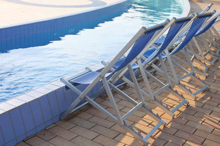deck chairs on the pool edge of the spa without people