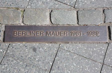 베를린 장벽의 길을 가리키는 보도에 박혀있는 커다란 기념패 스톡 콘텐츠