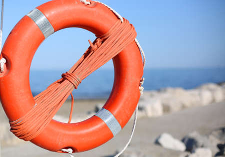 Orange lifebuoy for people near rocks at the sea in summer