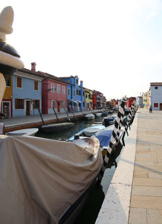 Boats moored in the navigable canal of Burano island near Venice in Northern Italy Banco de Imagens - 86034544