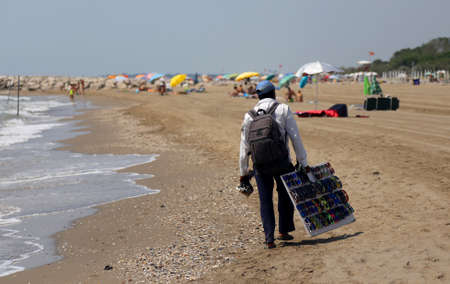 poor street vendor of clothes and dresses along the beach in summer