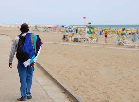 poor walking salesman along the beach in summer