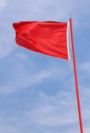 red waving flag indicating a state of danger and alarm with background of sky