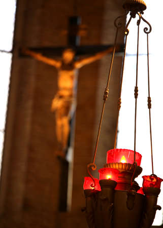 crucifix of a Christian church and candlestick with red candles