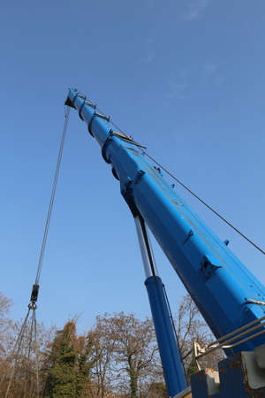 blue hydraulic arm of a powerful crane for lifting heavy loads at an industrial site Stock Photo