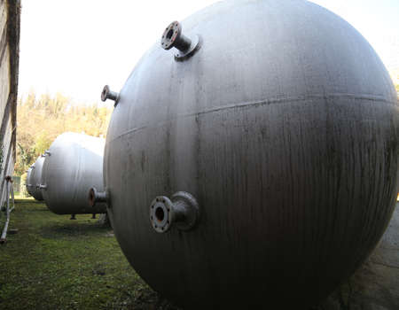 Huge gas storage tanks in an industrial area. Large cylinders are used to capture gas during energy crises or supply problems. Stock Photo