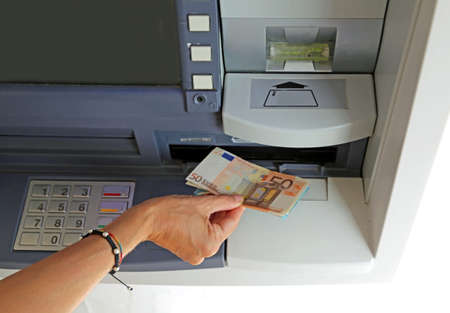 bankomat: hand of young woman while withdrawing banknotes 50 euros from an ATM in europe Stock Photo