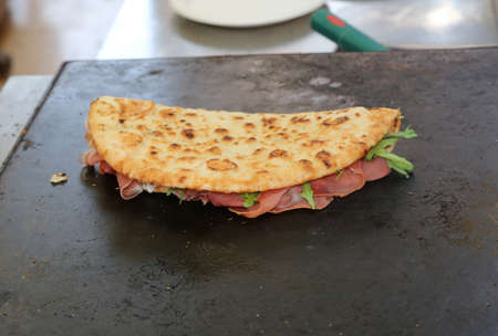 A tasty piadina that means flat bread in Italy stuffed with ham and rocket on the hot plate to bake Фото со стока
