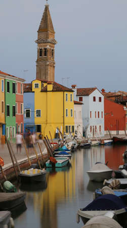 bell tower and navigable canal and the colorful houses of the BURANO island near Venice with moving boats due to the long exposure time