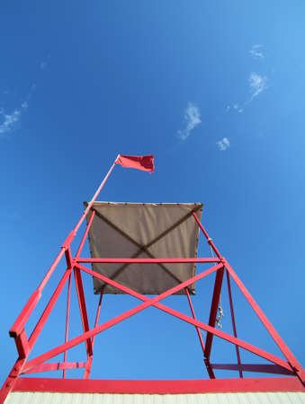high turret of lifeguard on the beach with the red flag to signal the danger