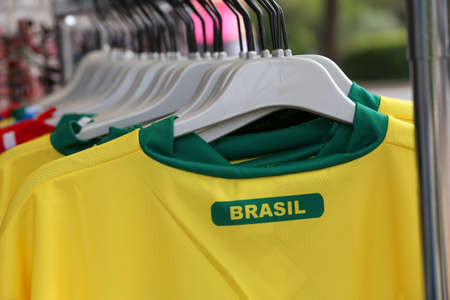 yellow and green t-shirts with the text BRASIL which means Brazil for sale in the specialized sports shop Stock Photo