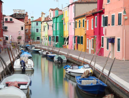 waterway  canal and the colorful houses of the BURANO island near Venice in Italy with moving boats due to the long exposure time of the photographic shot Imagens