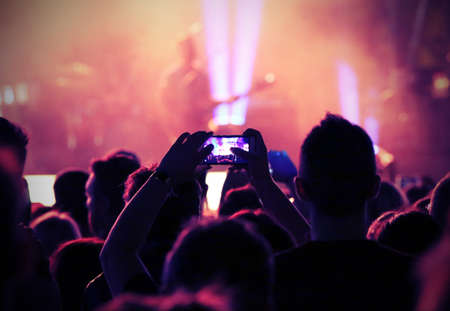 young fan takes a picture guitarist on stage during a live concert Stock Photo