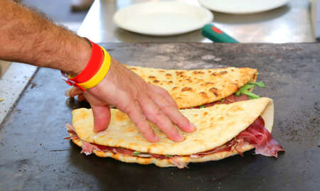 cook while baking the piadina that means flat bread in italian language on the hot plate in the street food stand