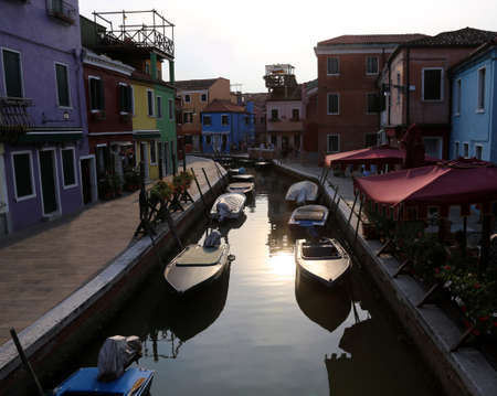Boats moored in the navigable canal of Burano island near Venice in Northern Italy