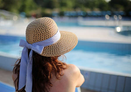 Beautiful woman with straw hat relaxes in the exclusive luxurious resort on the edge of the pool in summer