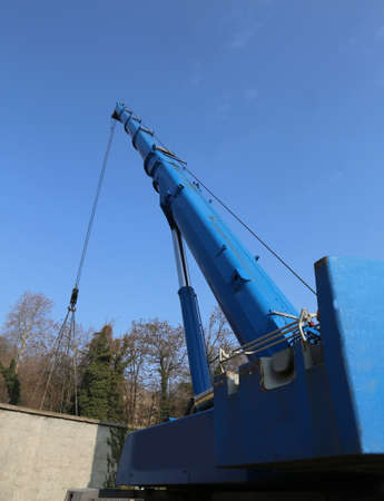 ample: blue hydraulic arm of a powerful crane for lifting heavy loads at an industrial site Stock Photo