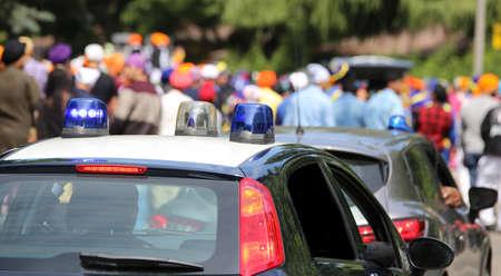 Autos policiales que encienden sirenas durante la manifestación de personas en las calles de la ciudad