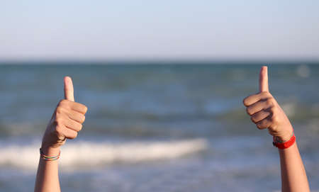 The little girls hands with her thumbs up and the background of the sea
