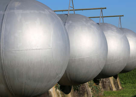 many huge tanks for the storage of methane gas in an industrial zone