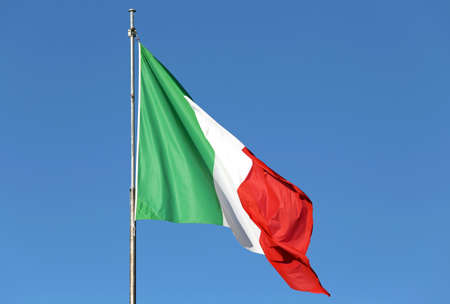 milánó: huge Italian flag waving with blue sky in the background Stock fotó