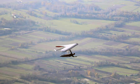 man flying high with hang glider above the plain. This is extreme sport Stock Photo