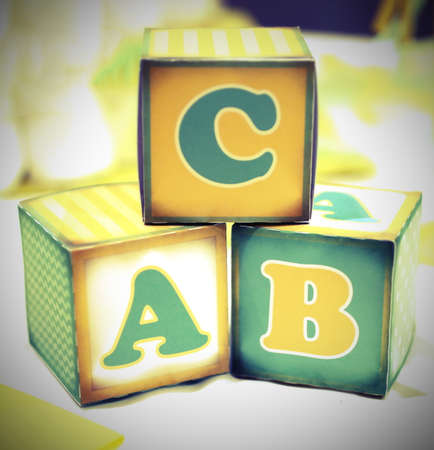 acquaint: three letter of the alphabet written on cubes of an old elementary school Stock Photo