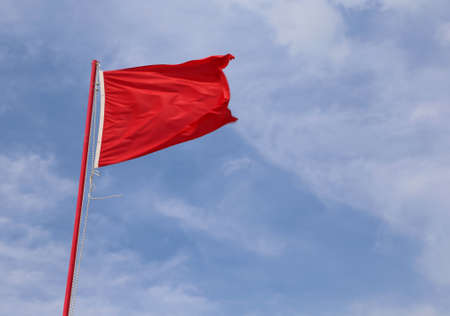 red flag indicating a state of danger and alarm with background of blue sky Banco de Imagens