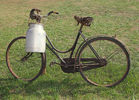 very old milking bicycle with aluminum milk canister to deliver milk just moistened