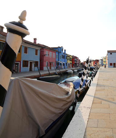 Boats moored in the navigable canal of Burano island near Venice in Italy