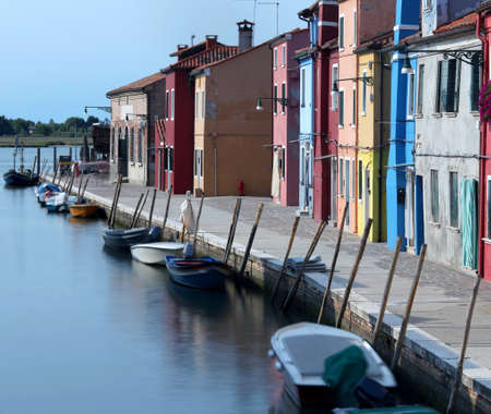 the navigable canal and the colorful houses of the BURANO island near Venice in Northern Italy with moving boats due to the long exposure time