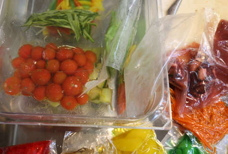 red tomatoes and other cooked vegetables in vacuum packed in special hermetic containers Stock Photo