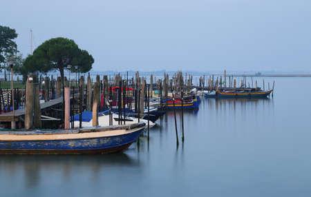 イタリアのヴェネツィアに近いブラーノ島の日の出でアドリア海で多くの船