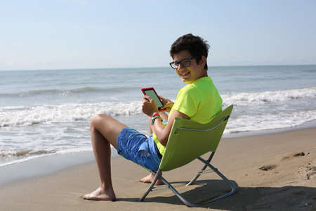 onderwijs: young boy reads a technological e-book at the seaside in summer with a fluorescent t-shirt Stockfoto
