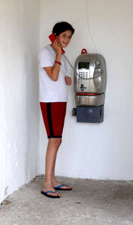 little boy on public phone in shorts