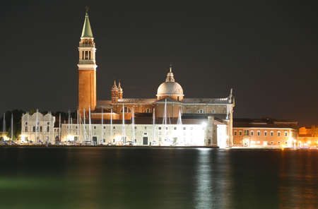 Venice Italy illuminated Church of Saint George called San Giorgio Maggiore in Italian Language by night and the reflection on the Venetian lagoon Stock Photo