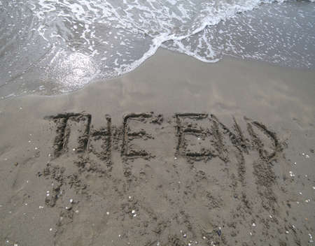text THE END written on the sand and the wave that is deleting the word can be used for the end of the presentations or at the end of a movie