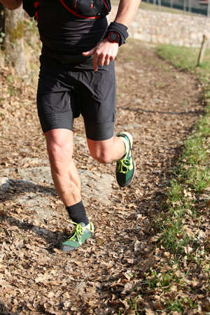 muscular athletes legs during the country race on the trail with the dry leaves