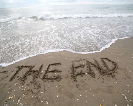 THE END text on the sand and the wave that is deleting the word can be used for the end of business presentations