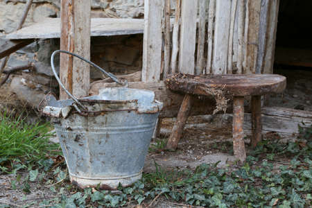 old broken tin bucket and an aluminum pot over the stool of the old abandoned stable Stock Photo