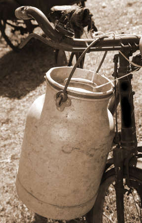 ancient milking bicycle with milk can and ancient sepia effect