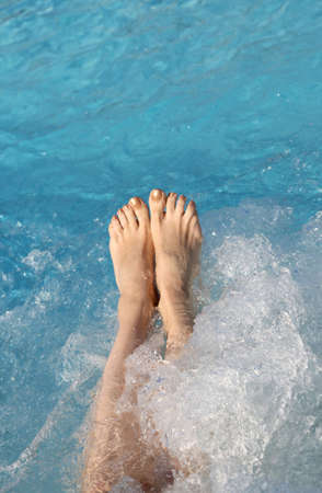 barefoot feet of a young woman during the whirlpool in the pool in a spa