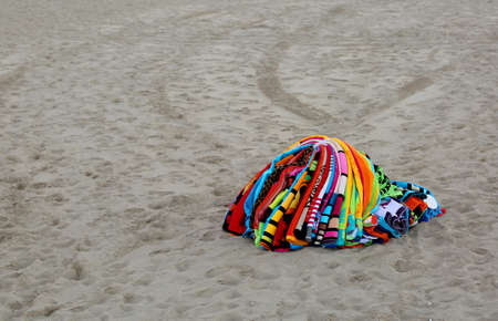 pile of towels abounding on the beach by an abusive seller after police raid