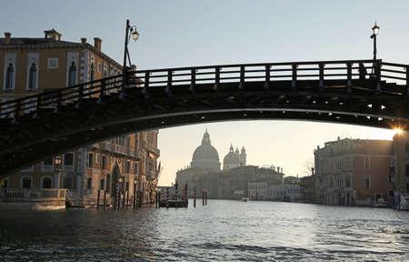 ancient wooden bridge in Venice Italy called Ponte della Accademia and the Church of Madonna della Salute on background Stock Photo - 88300640