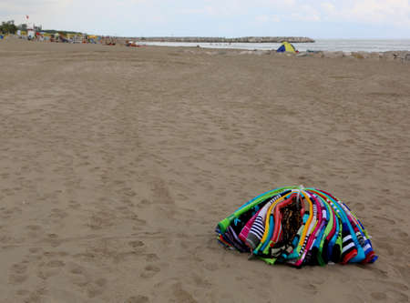 heap of colorful towels abounding on the beach by an abusive seller after police raid Imagens