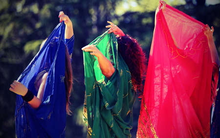 Three women during a sensual dance with long colorful clothes with vintage effect