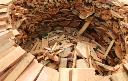circular wood-burning lumber with many logs of cut wood used to heat the wood-burning oven of a pizzeria