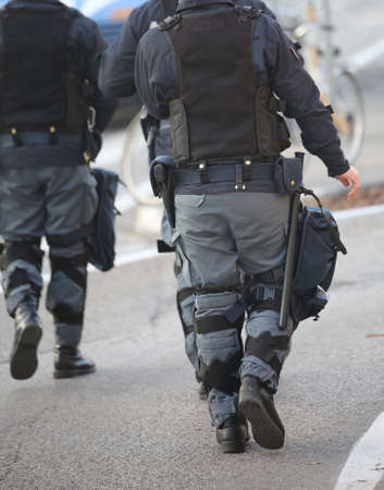 police patrol in riot police with gun and pistol during revolt in the city