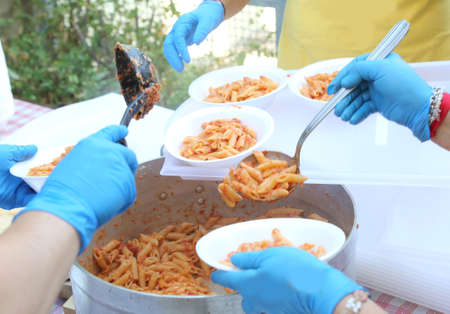 hands with blue latex gloves of the cooks during meal distribution of pasta with tomato sauce Stock Photo