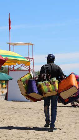 african abusive handbag seller in tourist resort beach